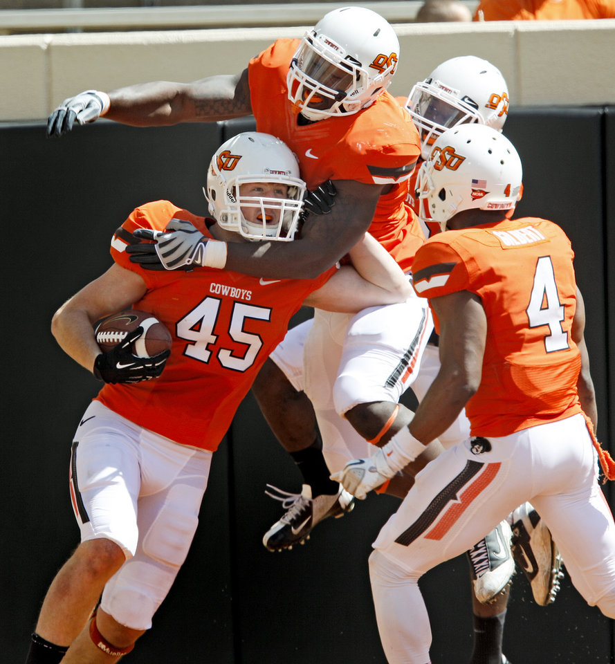 Oklahoma State\'s Caleb Lavey (45) celebrates with Sam Wren, top, and Larry Stephens, top right, after a 52-yard interception return for a touchdown during the OSU spring football game at Boone Pickens Stadium in Stillwater, Okla., Sat., April 20, 2013. Photo by Bryan Terry, The Oklahoman