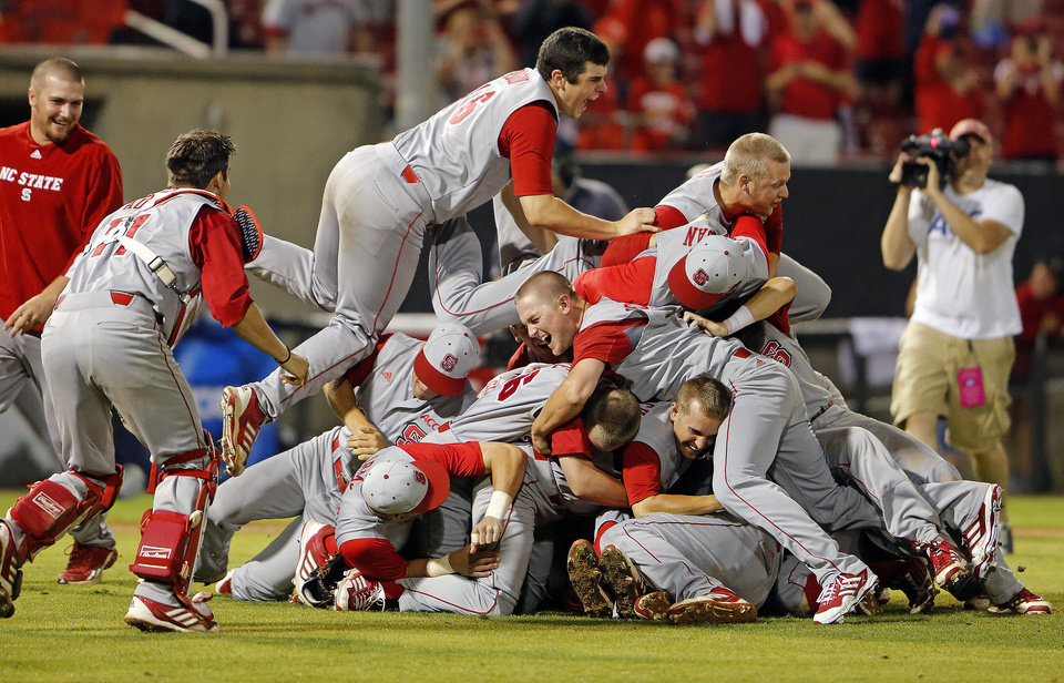 Photo - North Carolina State's Carlos Rodon (16) jumps on top of teammates as they celebrate their 5-4 win over Rice in the 17th inning of an NCAA college baseball tournament super regional game, Sunday, June 9, 2013, in Raleigh, N.C. (AP Photo/Karl B DeBlaker)
