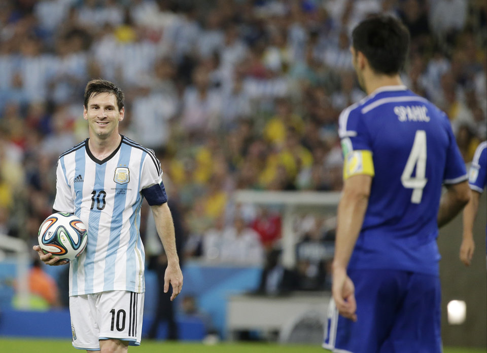 Photo - Argentina's Lionel Messi, left, smiles at Bosnia's Emir Spahic during the group F World Cup soccer match between Argentina and Bosnia at the Maracana Stadium in Rio de Janeiro, Brazil, Sunday, June 15, 2014.  (AP Photo/Felipe Dana)