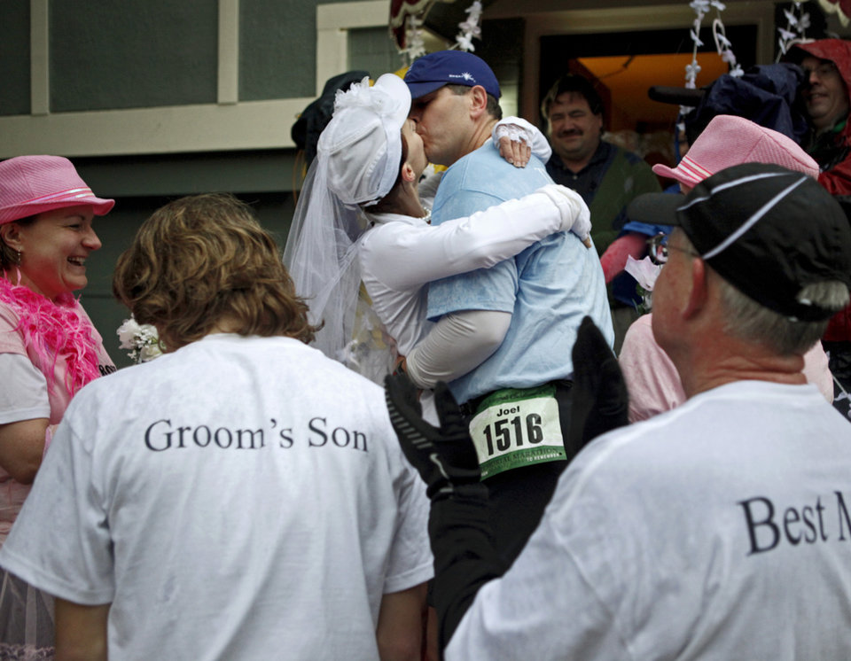 Photo - Joel Rogalsky and Amy Wills kiss after getting married during the Oklahoma City Memorial Marathon on NW 35th, Sunday, May 1, 2011. Photo by Bryan Terry, The Oklahoman