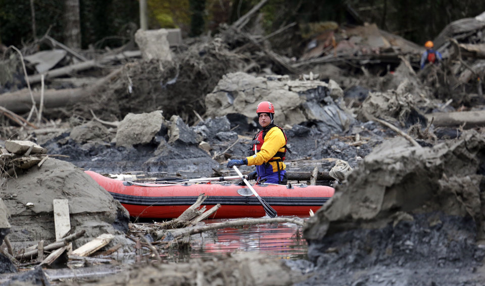 Photo - A searcher uses a small boat to look through debris from a deadly mudslide Tuesday, March 25, 2014, in Oso, Wash. At least 14 people were killed in the 1-square-mile slide that hit in a rural area about 55 miles northeast of Seattle on Saturday. Several people also were critically injured, and homes were destroyed. (AP Photo/Elaine Thompson)