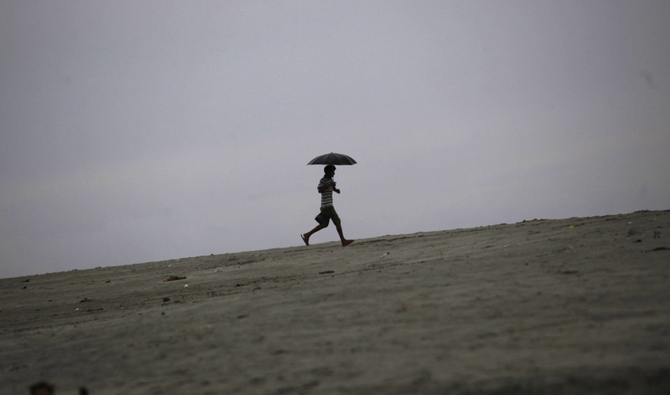 An Indian boy runs uphill along the banks of the River Brahmaputra as it rains in Gauhati, India, Thursday, May 16, 2013. Cyclone Mahasan weakened Thursday afternoon into a tropical storm and then dissipated, causing far less damage than had been feared as it passed over neighboring Bangladesh and spared Myanmar almost entirely, meteorological officials said. (AP Photo/Anupam Nath)