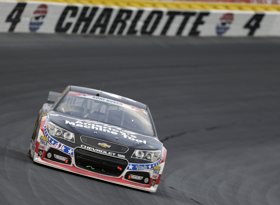 Photo - Kurt Busch (41) drives his car out of Turn 4 during the NASCAR Sprint Cup series Coca-Cola 600 auto race at Charlotte Motor Speedway in Concord, N.C., Sunday, May 25, 2014. (AP Photo/Chuck Burton)