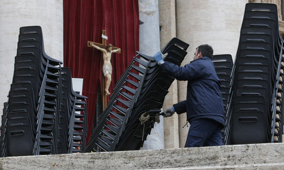 Photo - A worker places chairs in St. Peter's Square at the Vatican, Monday, March 18, 2013. The Vatican is releasing details of the pope's installation Mass on Tuesday as well images of his coat of arms and fisherman's ring. In addition to more than 132 government delegations, the Vatican said 33 Christian delegations will be present, as well as representatives from Jewish, Muslim, Buddhist, Sikh and Jain communities. (AP Photo/Dmitry Lovetsky)