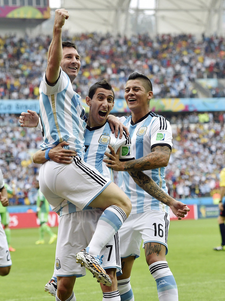 Photo - Argentina's Lionel Messi, left, is carried by his teammates Argentina's Angel di Maria (7) and Marcos Rojo (16) after scoring his side's first goal during the group F World Cup soccer match against Nigeria at the Estadio Beira-Rio in Porto Alegre, Brazil, Wednesday, June 25, 2014. (AP Photo/Martin Meissner)