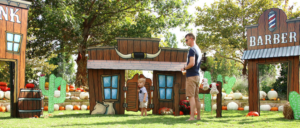 Photo - Alan Miner and his son Turner, 2 1/2, explore the western town during Pumpkinville in the Children's Area of the Myriad Botanical Gardens, Friday, October 6, 2017. Pumpkinville is open through October 22. Photo by Doug Hoke, The Oklahoman