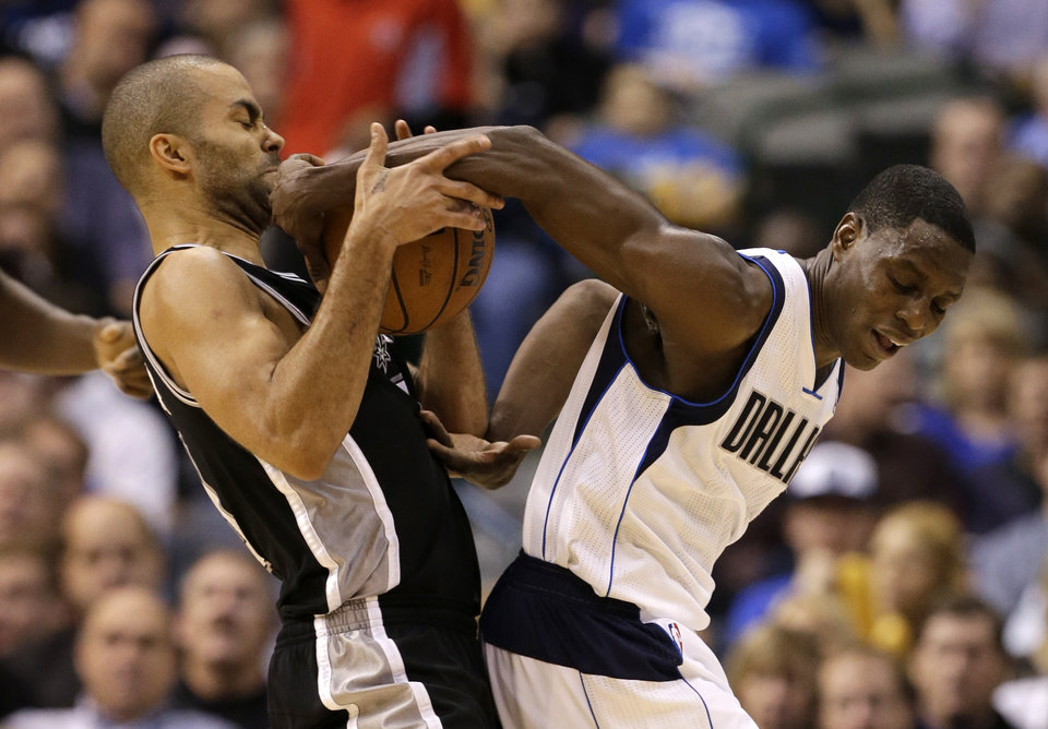 Photo - San Antonio Spurs' Tony Parker, left, of France, attempts to steal the ball away from Dallas Mavericks' Darren Collison, right, in the second half of an NBA basketball game on Friday, Jan. 25, 2013, in Dallas. Collison was able to retain control of the ball in the 113-107 Mavericks loss. (AP Photo/Tony Gutierrez)