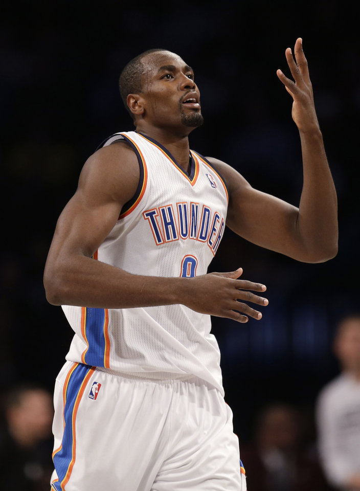 Photo - Oklahoma City Thunder's Serge Ibaka reacts after scoring during the second half of an NBA basketball game against the Brooklyn Nets, Friday, Jan. 31, 2014, in New York. The Thunder defeated the Nets 120-95. (AP Photo/Seth Wenig)