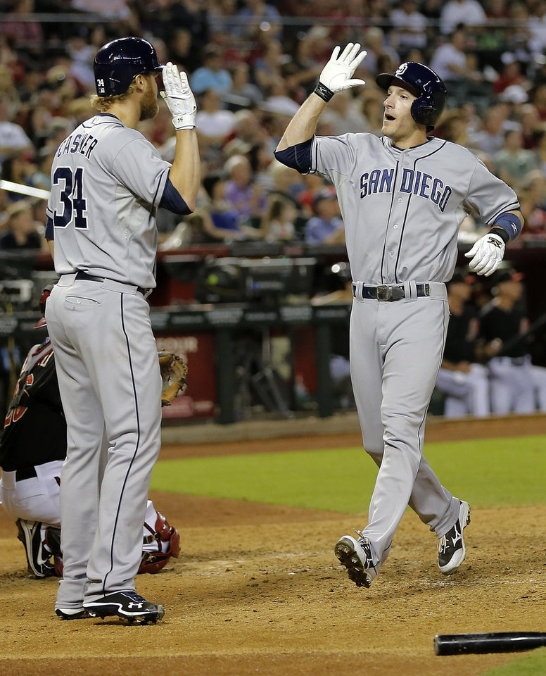 Photo - San Diego Padres' Chris Denorfia, right, high-fives teammate Andrew Cashner after both scored on a double by teammate Everth Cabrera during the fourth inning of a baseball game against the Arizona Diamondbacks, Saturday, May 25, 2013, in Phoenix. (AP Photo/Matt York)