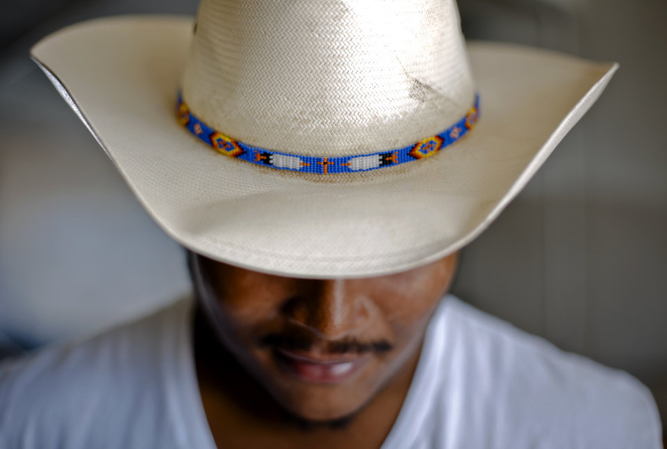 Photo - SUPER 30 / HIGH SCHOOL FOOTBALL PLAYER: Lawton High School's true country boy Ivan Thomas wears his cowboy hat with a hand beaded hat band with two eagles and a prayer cross made by his uncle on Tuesday, June 18, 2013 in Lawton, Okla.   Photo by Chris Landsberger, The Oklahoman