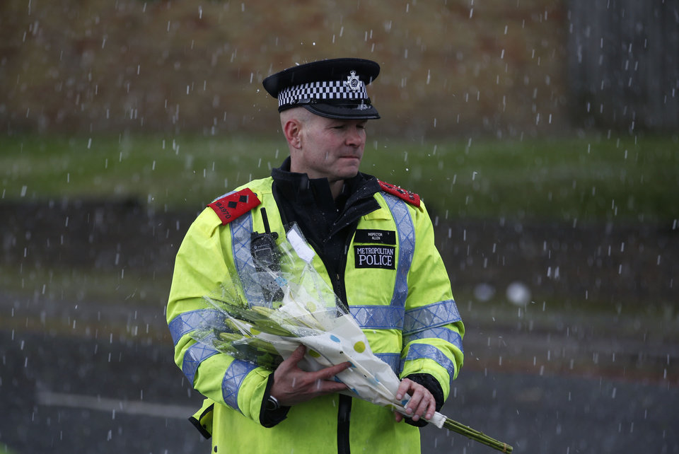 Photo - A police officer holds a floral tribute handed to him by a member of the public to be placed at the scene of a terror attack in Woolwich, southeast London, Thursday, May 23, 2013. The British government's emergency committee met Thursday after two attackers killed a man in a daylight attack in London that raised fears terrorism had returned to the capital.  (AP Photo/Sang Tan)