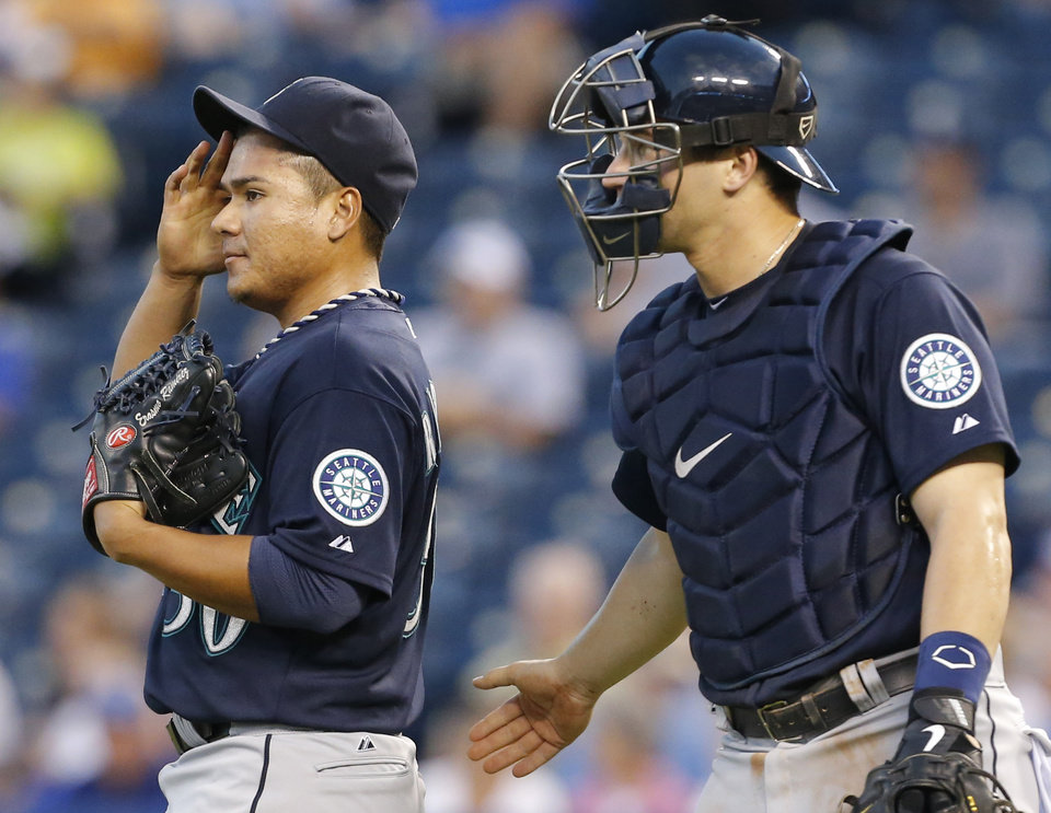 Photo - Seattle Mariners starting pitcher Erasmo Ramirez, left, wipes his forehead after talking with catcher Mike Zunino, right, in the second inning of a baseball game against the Kansas City Royals at Kauffman Stadium in Kansas City, Mo., Tuesday, Sept. 3, 2013. (AP Photo/Orlin Wagner)