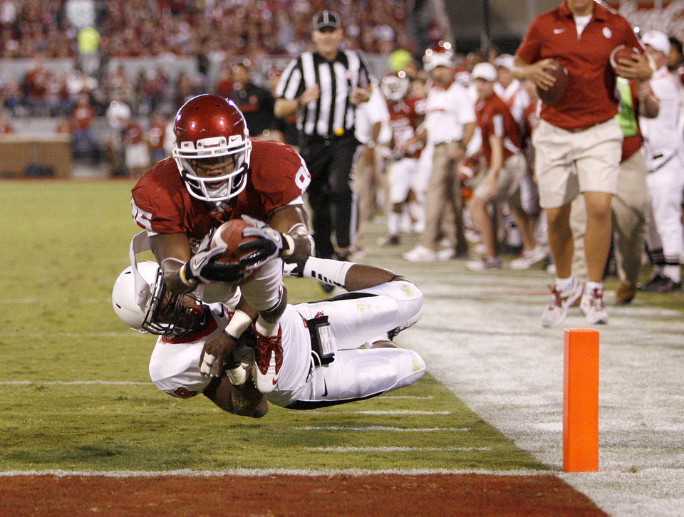 Photo - Oklahoma's Ryan Broyles (85) leaps for a touchdown past Ball State's Brian Jones (29) during the college football game between the University of Oklahoma Sooners (OU) and the Ball State Cardinals at Gaylord Family-Memorial Stadium on Saturday, Oct. 01, 2011, in Norman, Okla. Photo by Bryan Terry, The Oklahoman