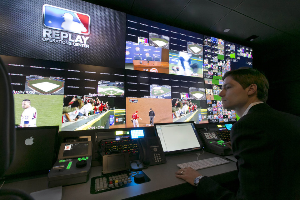 Photo - Chris Marinak sits in front of a bank of television screens during a preview of Major League Baseball's Replay Operations Center, in New York, Wednesday, March 26, 2014.  Less than a week before most teams open, MLB is working on the unveiling of its new instant replay system, which it hopes will vastly reduce incorrect calls by umpires. (AP Photo/Richard Drew)