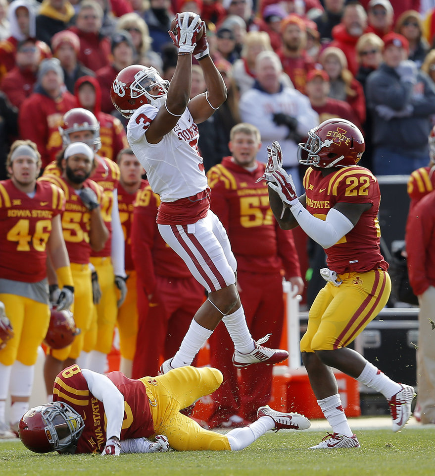 Photo - Oklahoma's Sterling Shepard (3) catches a pass between Iowa State's Kenneth Lynn (8) and T.J. Mutcherson (22) during a college football game between the University of Oklahoma Sooners (OU) and the Iowa State Cyclones (ISU) at Jack Trice Stadium in Ames, Iowa, Saturday, Nov. 1, 2014. Photo by Bryan Terry, The Oklahoman