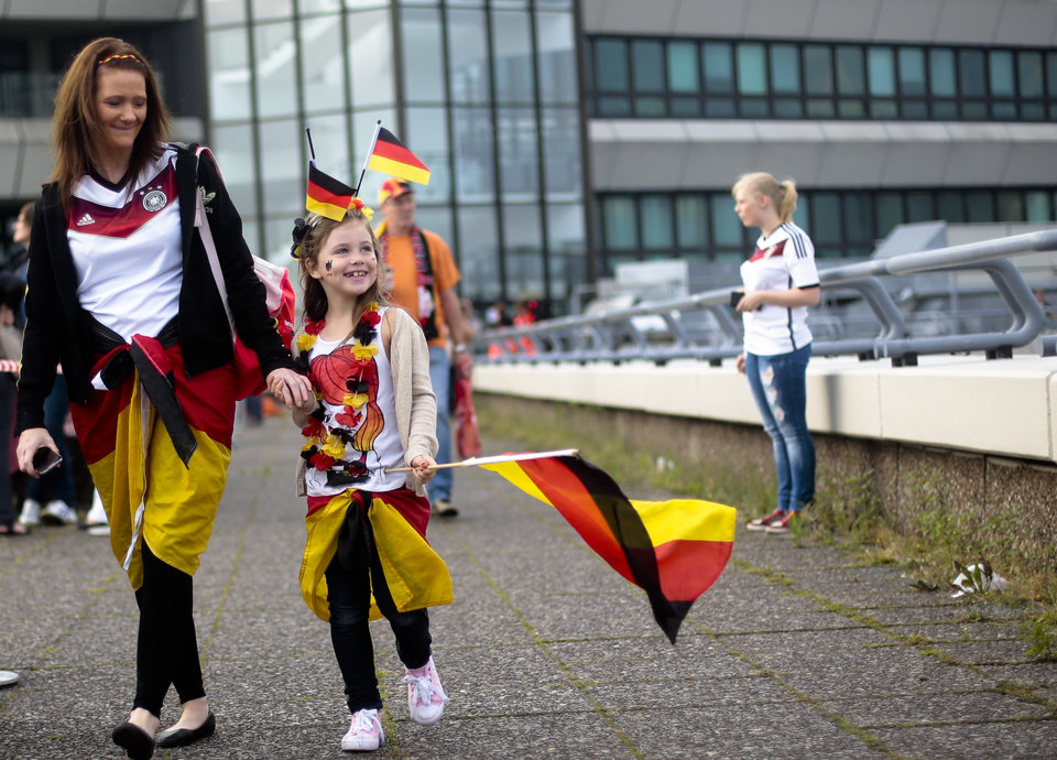Photo - Seven years old girl Charleen, center, arrives at the airport Tegel to welcome German national soccer team in Berlin Tuesday, July 15, 2014. Germany beat Argentina 1-0 on Sunday to win its fourth World Cup title.  (AP Photo/Markus Schreiber)