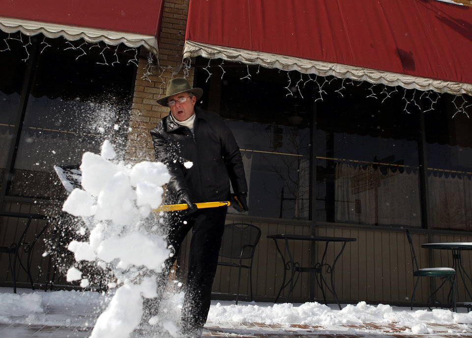 Photo - Bob Weiss, owner of Othello's, in downtown Edmond, Okla., shovels the sidewalk in front of his business, Wednesday, Feb. 9, 2011. Photo by Sarah Phipps, The Oklahoman