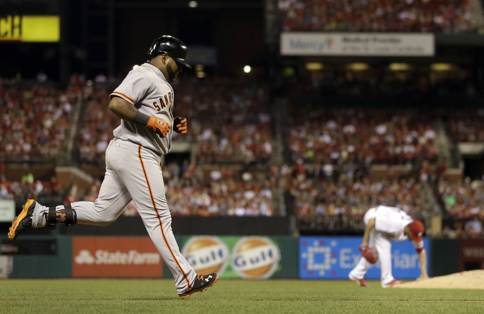 Photo - San Francisco Giants' Pablo Sandoval, left, rounds the bases after hitting a solo home run off St. Louis Cardinals starting pitcher Jaime Garcia during the sixth inning of a baseball game, Thursday, May 29, 2014, in St. Louis. (AP Photo/Jeff Roberson)