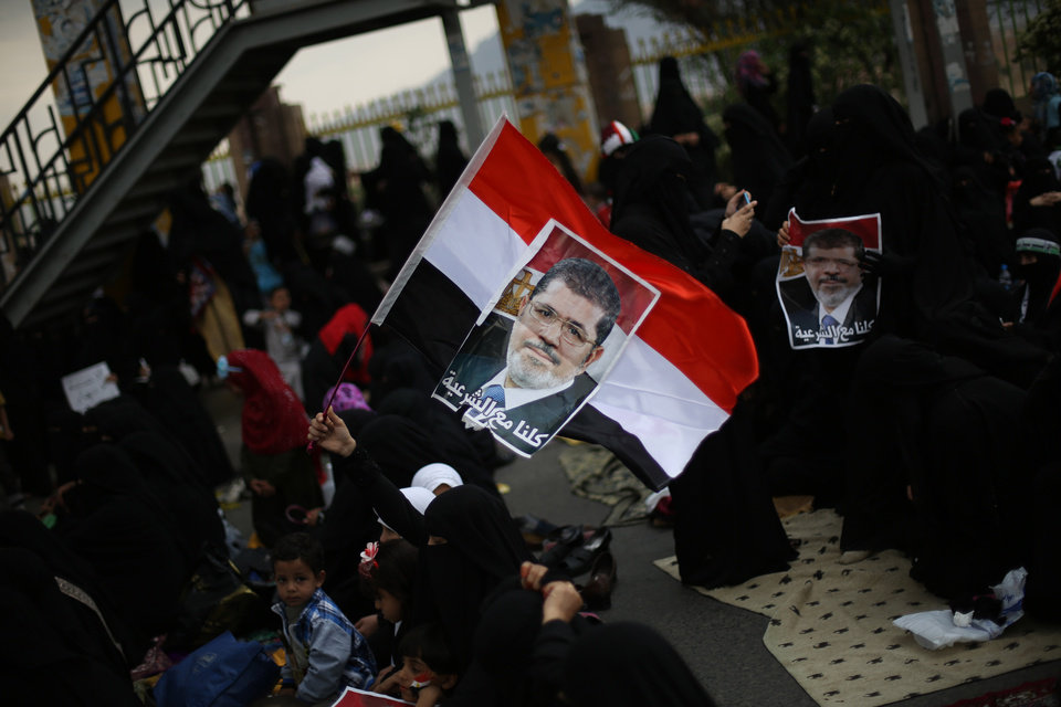 Photo - A woman holds a poster of Egypt's ousted President Mohammed Morsi pasted on a Yemeni flag as she and others attend a rally supporting Morsi in Sanaa, Yemen, Friday, Aug. 16, 2013. Arabic writing reads,