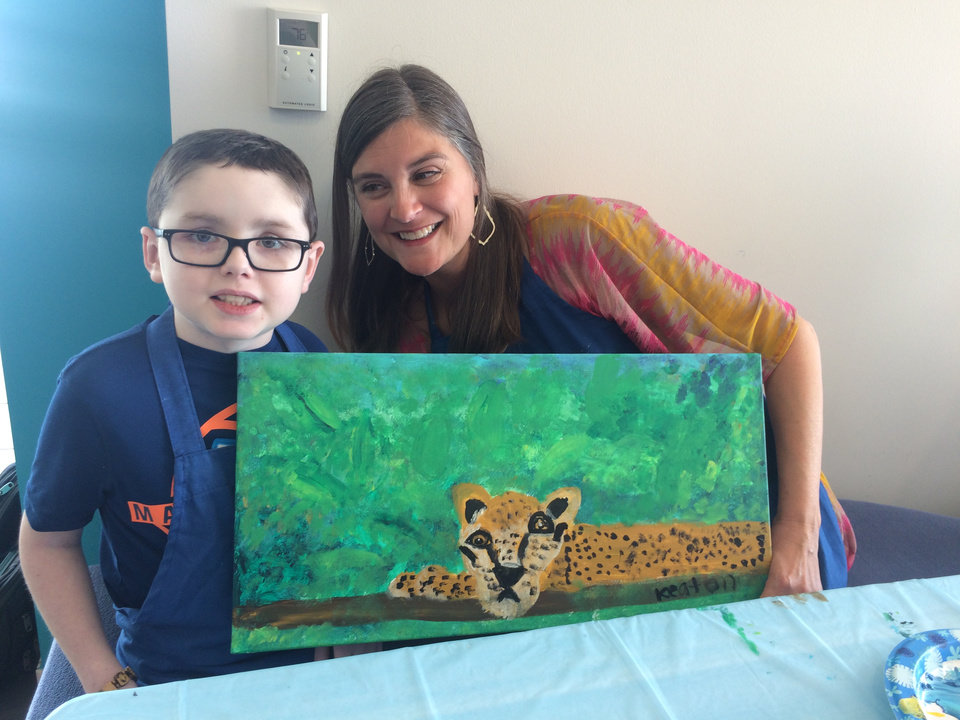 Photo -  Keaton Barron, 7, and Katherine Sanders, show his painting of a jaguar. Kids like Keaton worked with adult artists to produce pieces that will go up for auction at the Art with a Heart cancer fundraiser. [Photo provided by Holly Barron]