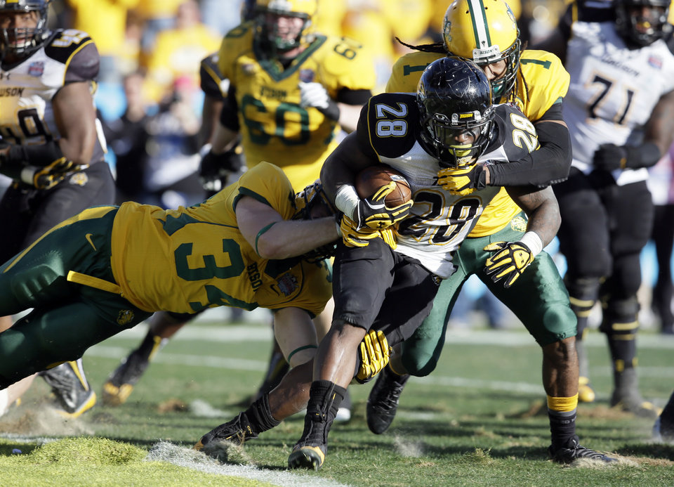 Photo - Towson running back Terrance West (28) fights his way out of the end zone avoiding a safety as North Dakota State's Grant Olson (34) and Marcus Williams (1) make the stop in the second half of the FCS championship NCAA college football game, Saturday, Jan. 4, 2014, in Frisco, Texas. NDSU won 35-7. (AP Photo/Tony Gutierrez)