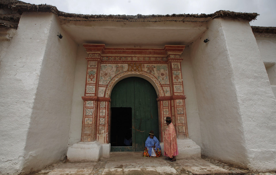 Two Aymara women stand at the door of the Sistine Chapel of Los Andes in Curahuara de Carangas,  Oruro department, 260 km. (160 miles) south from La Paz, Bolivia, Saturday, Dec. 8, 2012. Built in 1608 to evangelize indigenous Bolivians into the Roman Catholic faith, the chapel these days attracts both the faithful and tourists. (AP Photo/Juan Karita)
