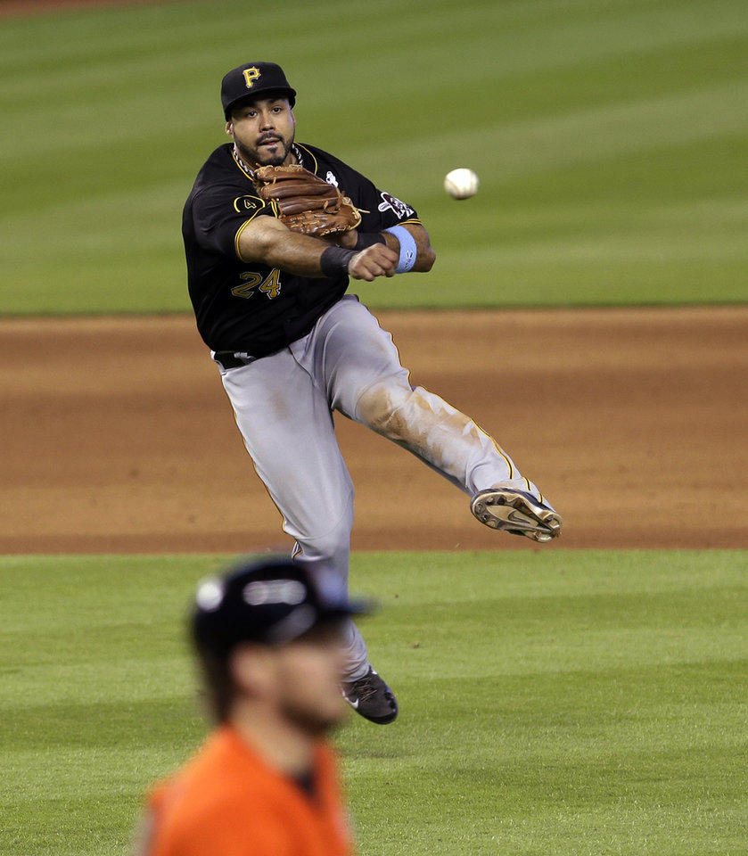 Photo - Pittsburgh Pirates third baseman Pedro Alvarez (24) throws to first base after fielding a ground ball hit by Miami Marlins' Jeff Mathis, bottom, in the ninth inning of a baseball game in Miami, Sunday, June 15, 2014. Mathis was out at first base. The Marlins won 3-2. (AP Photo/Alan Diaz)