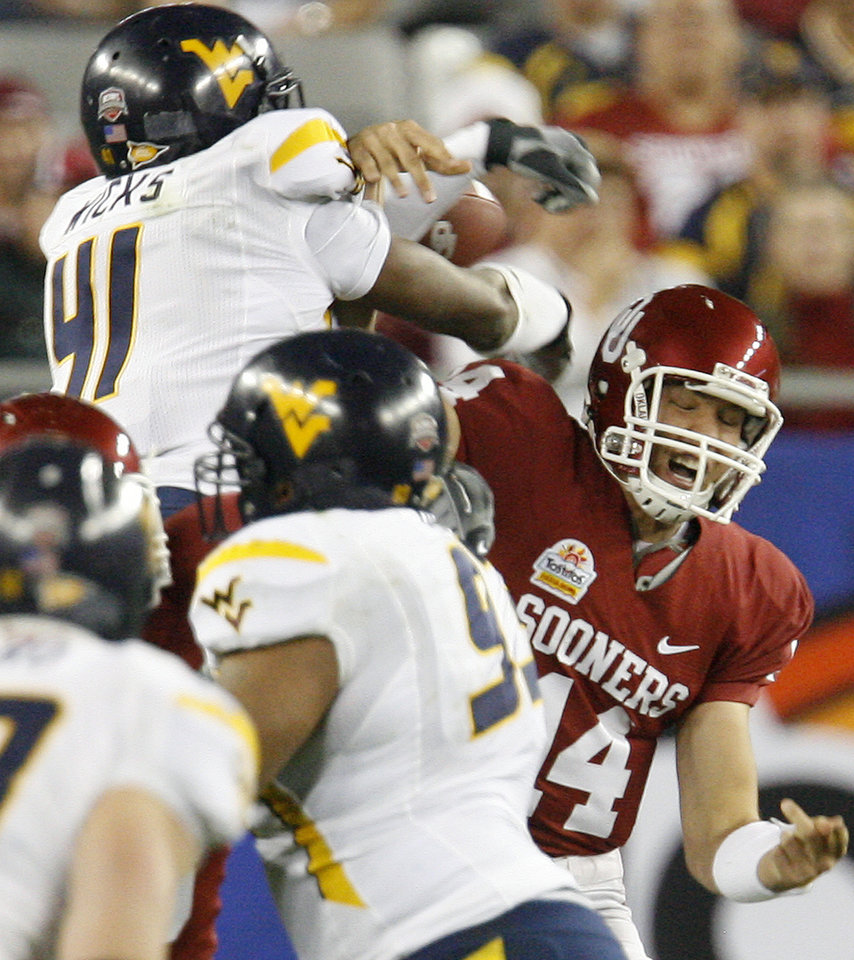Photo - Oklahoma's Sam Bradford (14) is hit by West Virginia's Eric Ricks (41) during the first half of the Fiesta Bowl college football game between the University of Oklahoma Sooners (OU) and the West Virginia University Mountaineers (WVU) at The University of Phoenix Stadium on Wednesday, Jan. 2, 2008, in Glendale, Ariz.   BY BRYAN TERRY, THE OKLAHOMAN ORG XMIT: KOD