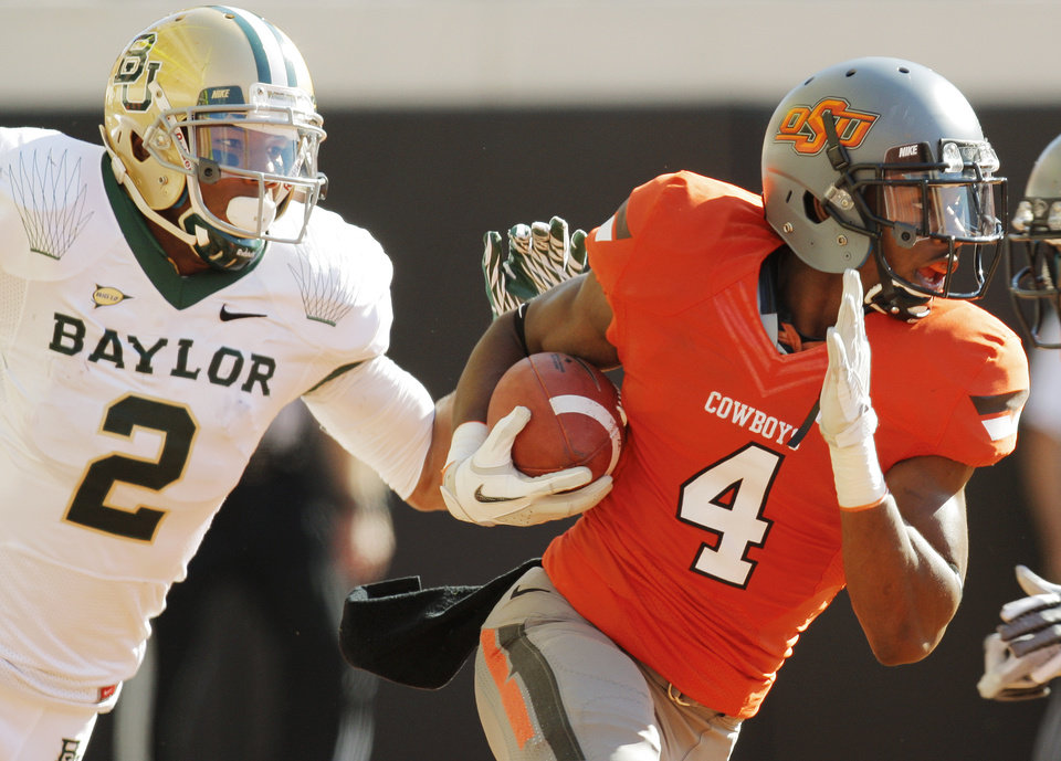Photo - OSU's Justin Gilbert (4) returns an intercepted Baylor pass from the end zone past Terrance Williams (2) of Baylor  in the second quarter during a college football game between the Oklahoma State University Cowboys (OSU) and the Baylor University Bears (BU) at Boone Pickens Stadium in Stillwater, Okla., Saturday, Oct. 29, 2011. Photo by Nate Billings, The Oklahoman ORG XMIT: KOD