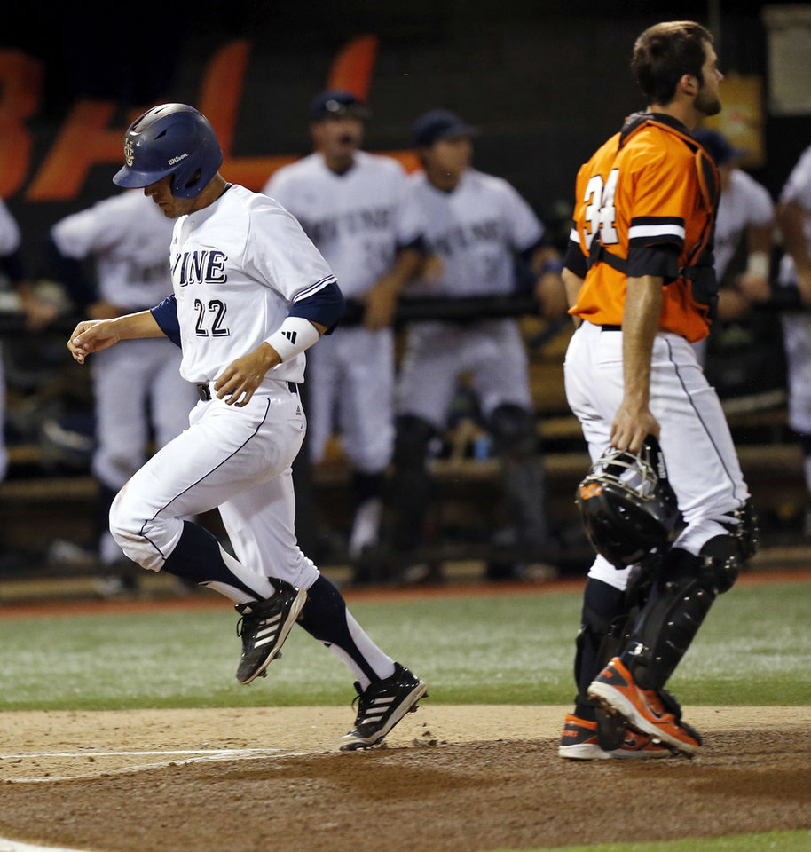 Photo - UC Irvine's Chris Rabago (22) scores past OSU's Bryan Case (34) in the bottom of the first inning during Game 2 of the NCAA baseball Stillwater Super Regional between Oklahoma State and UC Irvine at Allie P. Reynolds Stadium in Stillwater, Okla., Saturday, June 7, 2014. Photo by Nate Billings, The Oklahoman