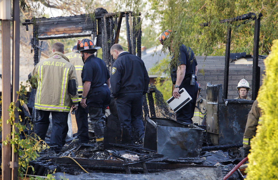 Photo -  Firefighters investigate a fatal house fire Tuesday in Oklahoma City. Photo by Paul B. Southerland, The Oklahoman   PAUL B. SOUTHERLAND -