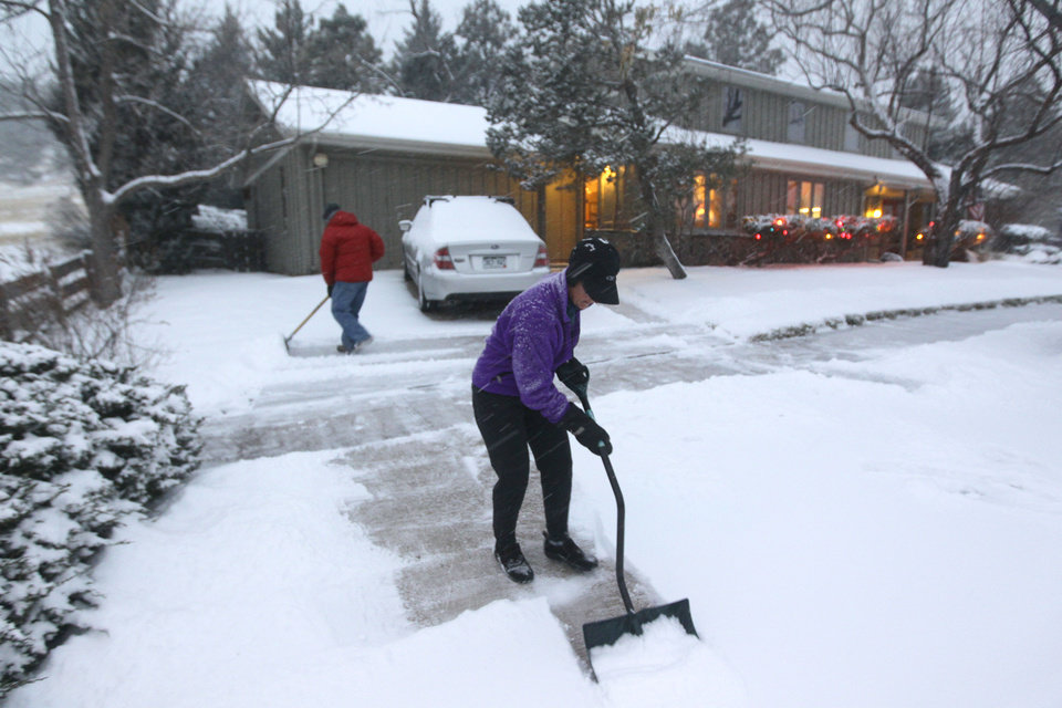 Photo - A woman and her husband shovel their walk as a blizzard dropped snow over Boulder, Colo., Wednesday Dec. 19, 2012. A storm that has dumped more than a foot of snow in the Rocky Mountains is heading east and is forecast to bring the first major winter storm of the season to the central plains and Midwest. (AP Photo/Brennan Linsley)