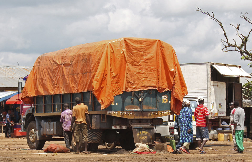 Photo - In this Tuesday, Aug. 19, 2014 photo, people walk around a truck parked at one of the largest trading areas catering for people from the Kambia District, Guiea. Since the Ebola virus outbreak the boarder has been closed with the local population's movement stopped as an attempt to stop the virus spreading in Kambia. Kambia district provides an important trade route to or from Guinea's capital Conakry and Sierra Leone's capital Freetown. (AP Photo/Youssouf Bah)