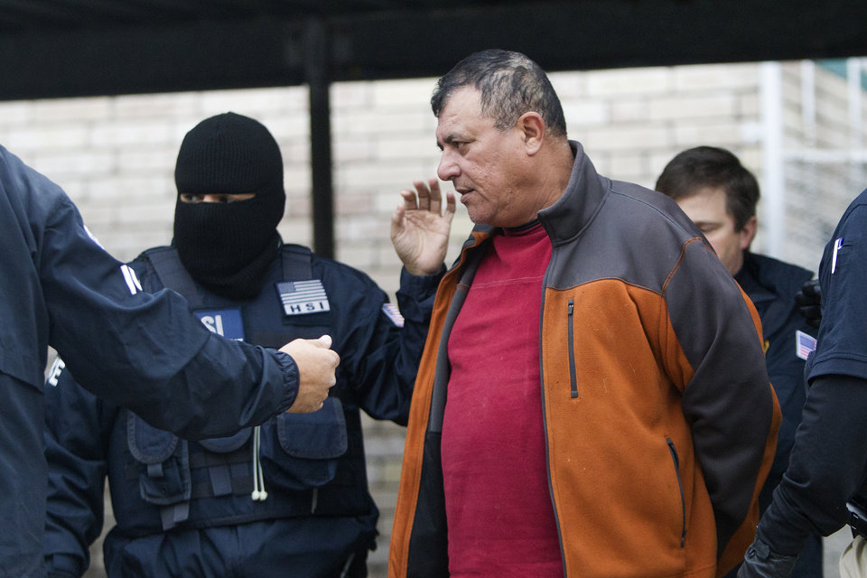 Photo - Federal authorities take a man into custody after raiding a business, Thursday, Jan. 30, 2014, in southwest Houston. Authorities served search warrants at two businesses in the Chinatown area detaining people in a crackdown on an alleged human smuggling ring operating in Texas and other states. (AP Photo/Houston Chronicle, Cody Duty)