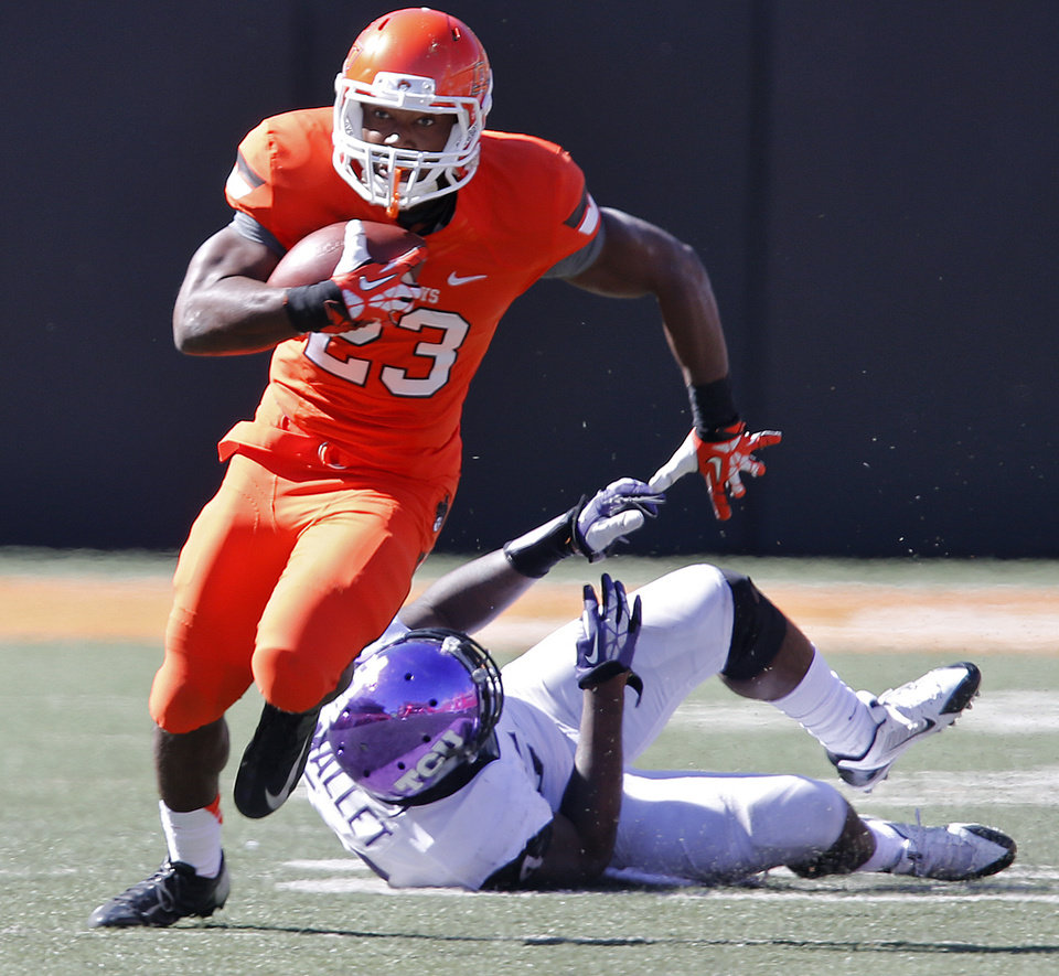 Oklahoma State's Rennie Childs (23) runs past TCU's Marcus Mallet (54) during a college football game between the Oklahoma State University Cowboys (OSU) and the Texas Christian University Horned Frogs (TCU) at Boone Pickens Stadium in Stillwater, Okla., Saturday, Oct. 19, 2013. Photo by Chris Landsberger, The Oklahoman