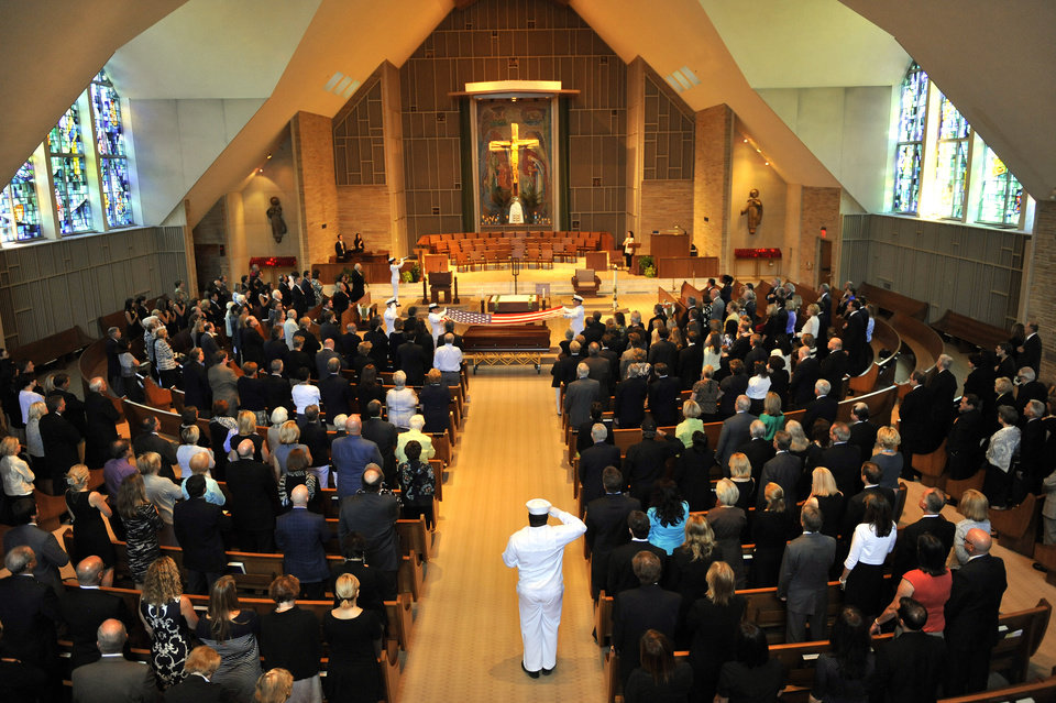Guests stand at attention as U.S. Naval officers drape Elmore Leonard's casket with an American flag during the military honors portion of his funeral mass inside Holy Name Church in Birmingham, Mich., Saturday Aug. 24, 2013. Leonard served in the Navy during World War II. The beloved Metro-Detroit crime novelist died Tuesday at his home in Bloomfield Village at age 87. (AP Photo/The Detroit News, John T. Greilick)
