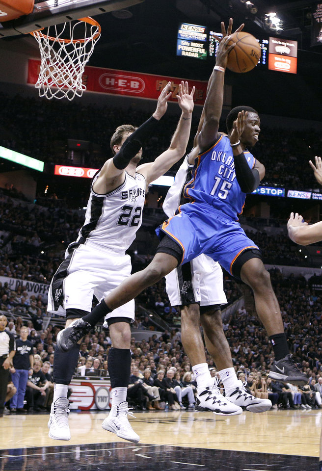 Photo - Oklahoma City's Reggie Jackson (15) looks to pass the ball as San Antonio's Tiago Splitter (22) defends during Game 1 of the Western Conference FInals in the NBA playoffs between the Oklahoma City Thunder and the San Antonio Spurs at the AT&T Center in San Antonio, Monday, May 19, 2014. Photo by Sarah Phipps, The Oklahoman