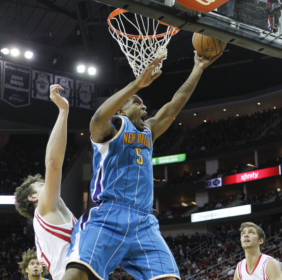 New Orleans Hornets small forward Dominic McGuire (5) drives to the basket for a layup past Houston Rockets center Omer Asik (3) during the first half of an NBA basketball game on Wednesday, Jan. 2, 2013, in Houston. (AP Photo/Bob Levey)