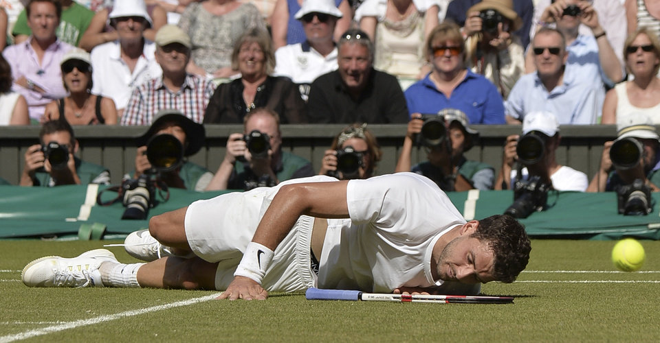 Photo - Grigor Dimitrov of Bulgaria lies on the ground after falling as he attempted to return the ball to Novak Djokovic of Serbia during their men's singles semifinal match at the All England Lawn Tennis Championships at Wimbledon, London, Friday, July, 4, 2014. (AP Photo/Anthony Devlin, Pool)