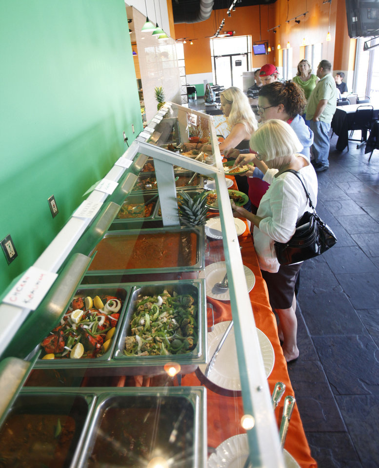 Photo - Customers pass through the buffet at Heritage India, a new Indian restaurant in Edmond  PAUL HELLSTERN - Oklahoman