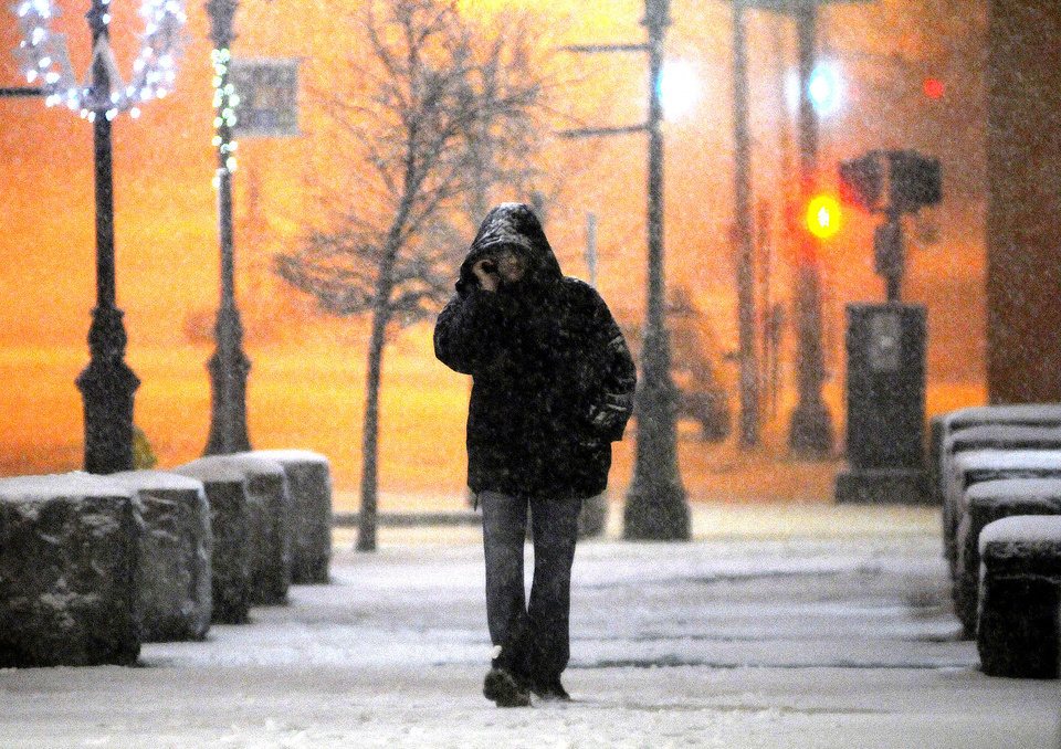 Photo - In this Wednesday, Dec. 26, 2012 photo, a man talks on his cellphone, as he walks along Main Street during a snowstorm late Wednesday night.  The winter storm brought snow to inland parts of the Northeast and driving rain and wind to areas along the coast Thursday, a day after it swept through the nation's middle, dumping a record snowfall in Arkansas and wrecking post-holiday plans for thousands of travelers.  (AP Photo/The Telegram & Gazette, Steve Lanava)