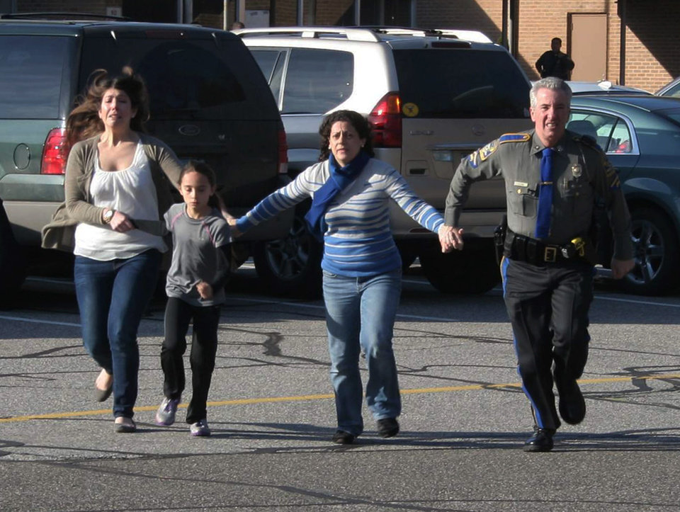 Photo - In this photo provided by the Newtown Bee, a police officer leads two women and a child from Sandy Hook Elementary School in Newtown, Conn., where a gunman opened fire, killing 26 people, including 20 children, Friday, Dec. 14, 2012. (AP Photo/Newtown Bee, Shannon Hicks) MANDATORY CREDIT: NEWTOWN BEE, SHANNON HICKS