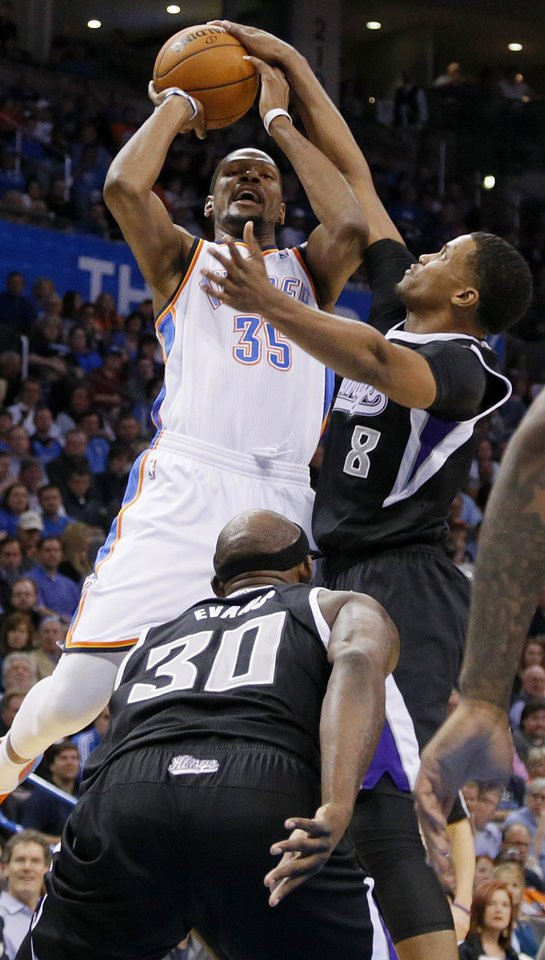 Photo - Oklahoma City's Kevin Durant (35) is fouled by Sacramento's Rudy Gay (8) during an NBA game between the Oklahoma City Thunder and the Sacramento Kings at Chesapeake Energy Arena in Oklahoma City, Friday, March 28, 2014. Photo by Bryan Terry, The Oklahoman