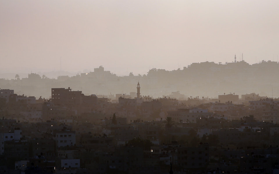 Photo - Hazy Gaza City is seen in northern Gaza strip early Saturday, July 19, 2014. Israeli troops pushed deeper into Gaza on Friday in a ground offensive that officials said could last up to two weeks as the prime minister ordered the military to prepare for a