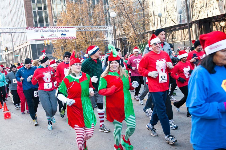 Photo - Participants run, jog and walk during the SandRidge Santa Run, part of Downtown in December. Photo provided.