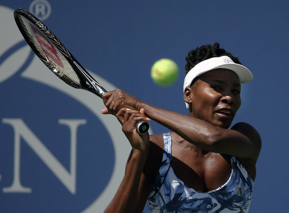 Photo - Venus Williams, of the United States, returns a shot against Kimiko Date-Krumm, of Japan, during the opening round of the 2014 U.S. Open tennis tournament, Monday, Aug. 25, 2014, in New York. (AP Photo/Elise Amendola)