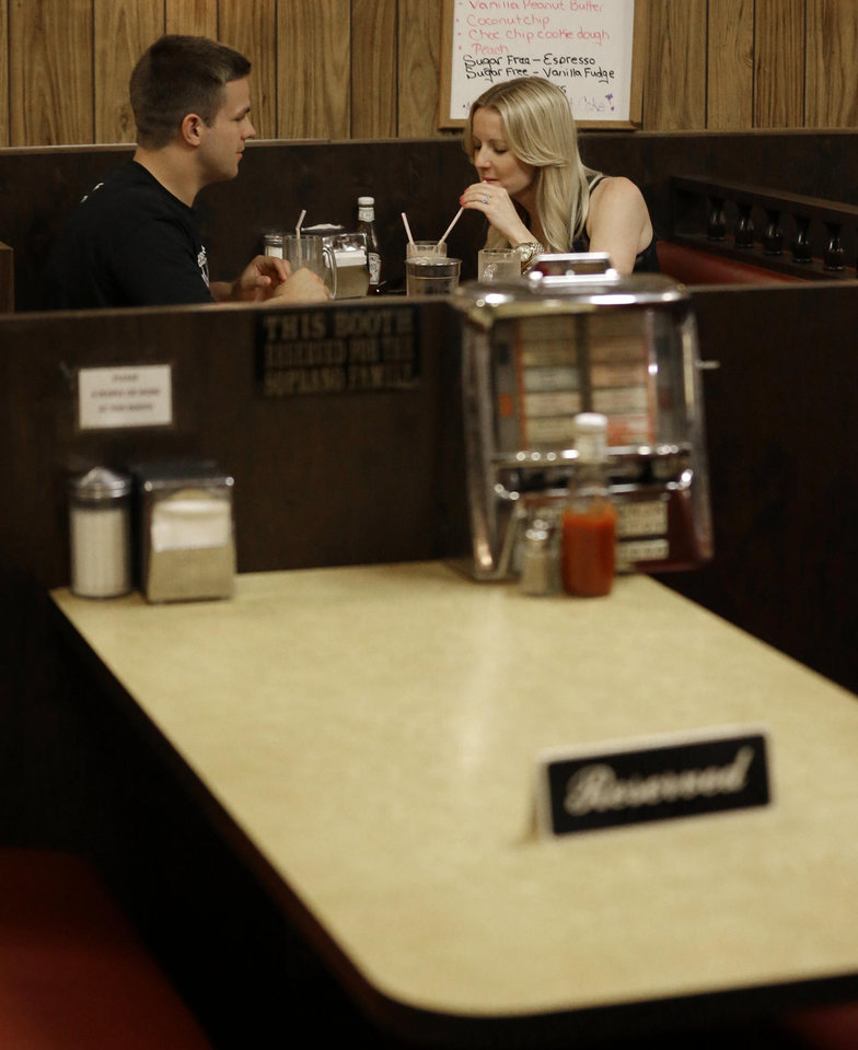 "Jeff Martin, left, and his wife Sheryl Martin eat at Holsten's ice cream parlor as an empty booth where the last show of the HBO series ""The Sopranos"" was filmed is seen with a reserved sign, Wednesday, June 19, 2013, in Bloomfield, N.J. The sign was put on the booth where the last scene was filmed in honor of actor James Gandolfini who died Wednesday in Italy. He was 51. (AP Photo/Julio Cortez)"