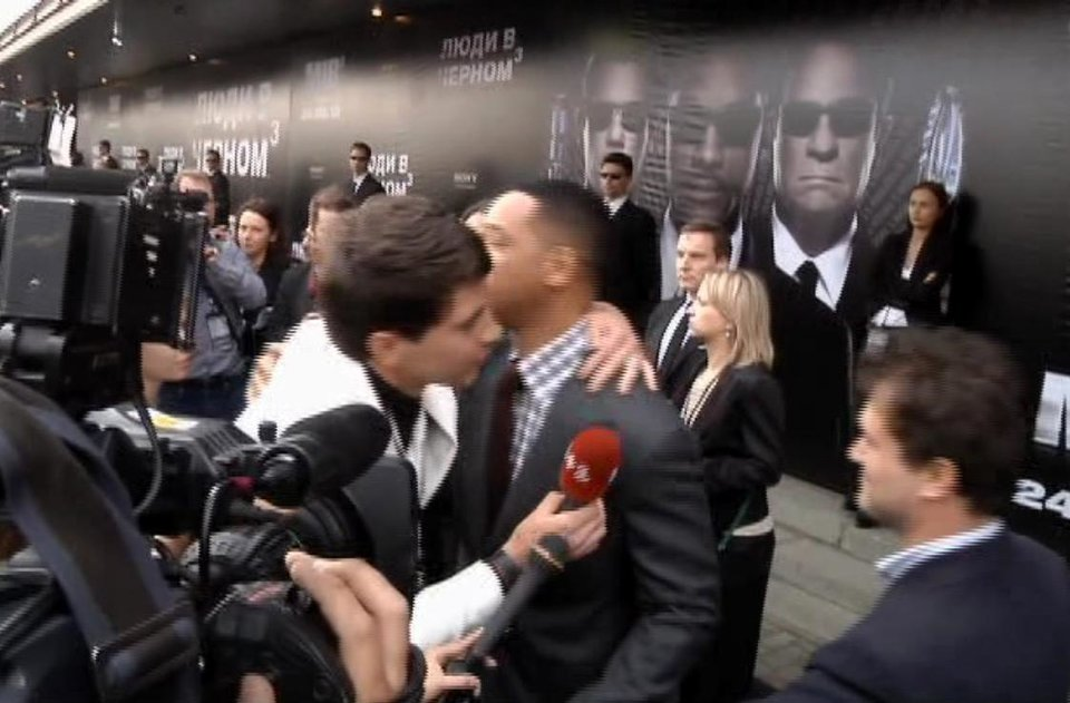 Photo -   In this video image taken from AP video U.S. actor Will Smith, center right, is embraced by reporter Vitalii Sediuk, white suit, from the Ukrainian television channel 1+1 on the red carpet before the premiere of