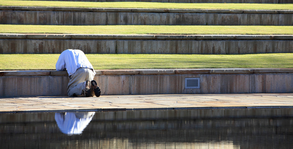 A man kneels by the reflecting pool before the18th Anniversary Remembrance Ceremony at the Oklahoma City National Memorial and Museum, Friday, April 19, 2013. Photo By David McDaniel/The Oklahoman