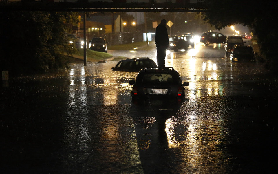Photo - A man stands on top of his car as it is flooded on S. May Avenue near SW 25th in Oklahoma City, Friday, May 31, 2013, after severe weather moved through the area. (AP Photo/The Oklahoman, Sarah Phipps) LOCAL STATIONS OUT (KFOR, KOCO, KWTV, KOKH, KAUT OUT); LOCAL WEBSITES OUT; LOCAL PRINT OUT (EDMOND SUN OUT, OKLAHOMA GAZETTE OUT) TABLOIDS OUT